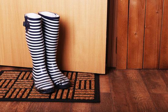 Dirty wellington boots on door mat in hallway
