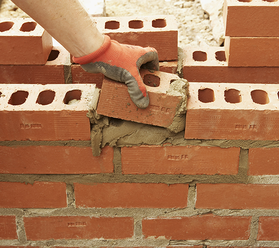 Bricklayer inserts a half brick into a wall