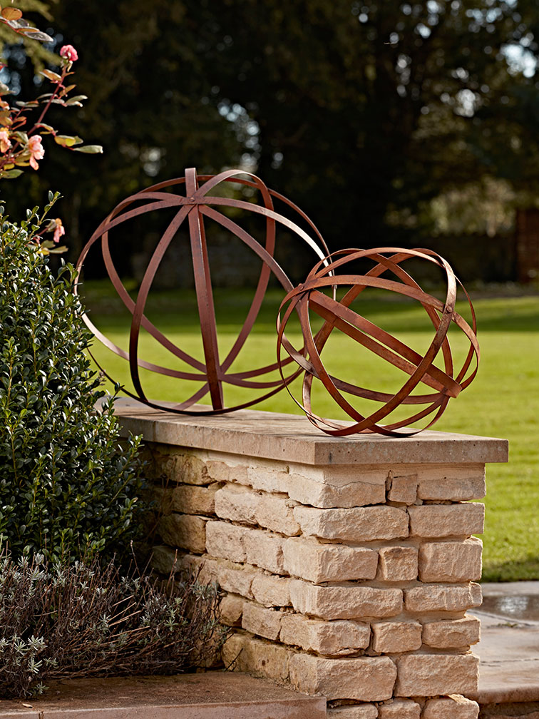two rusty sphere garden decorations