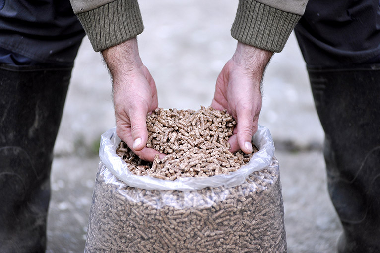 Person taking wood pellets from a bag