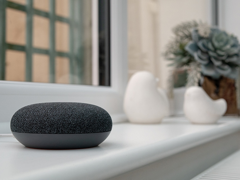 Grey smart speaker on white window ledge