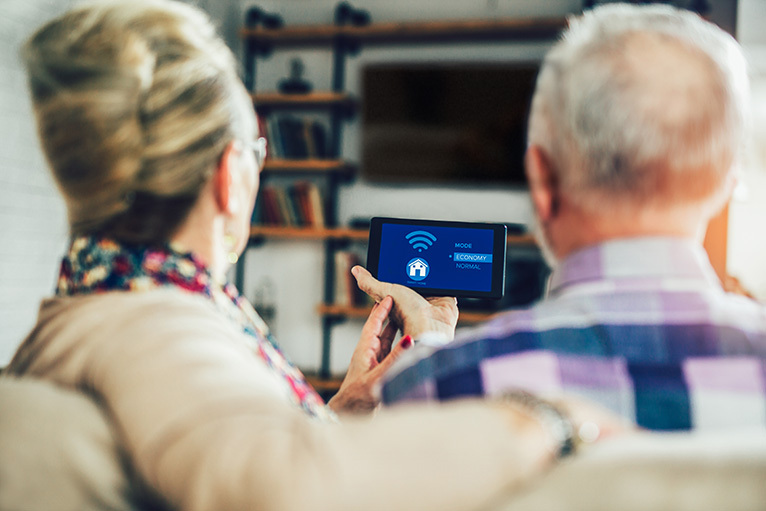 Older couple operating home tech from a phone