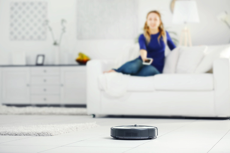 Girl on sofa operating a robot vacuum cleaner