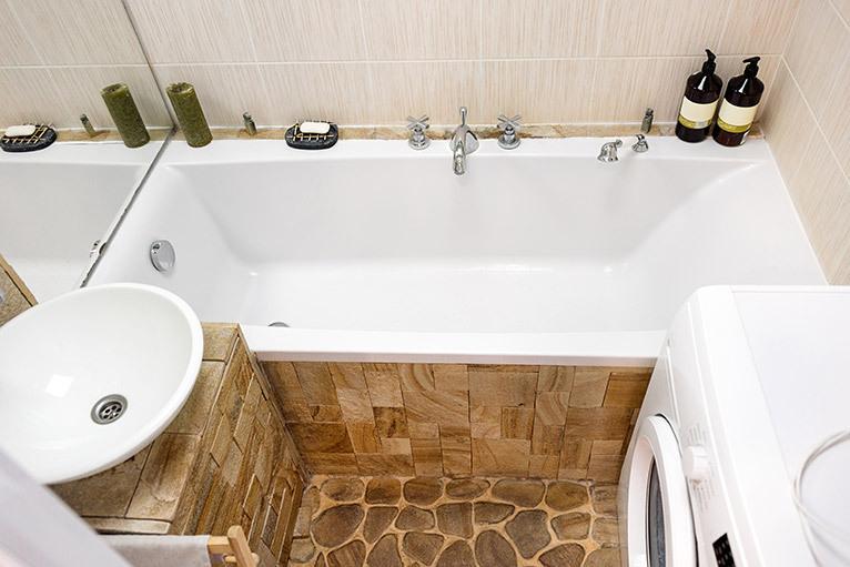 Small bathroom with sink, bath and washing machine