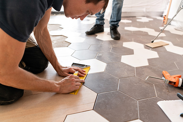 Tiler fitting hexagonal floor tiles