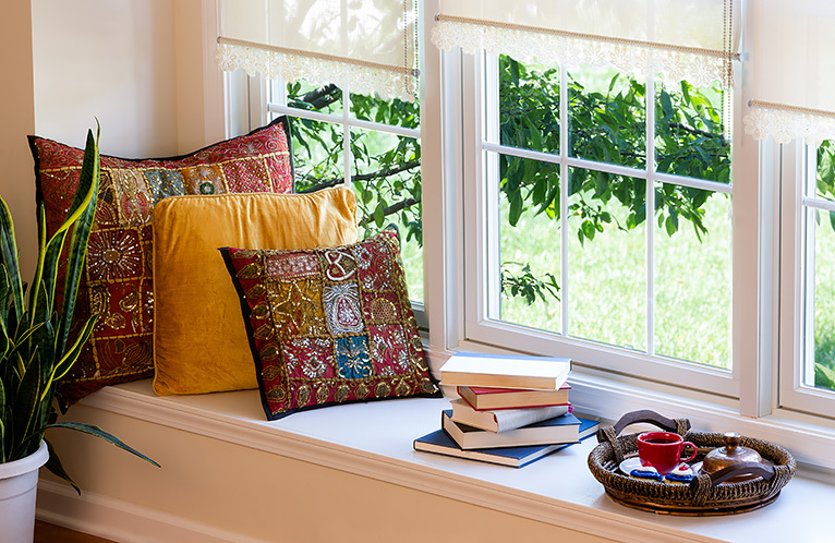 Window with cushions and books on a wide sill