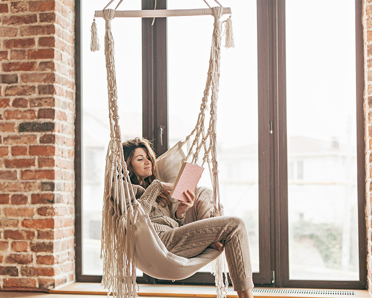 Girl reading in a hammock chair suspended from the ceiling