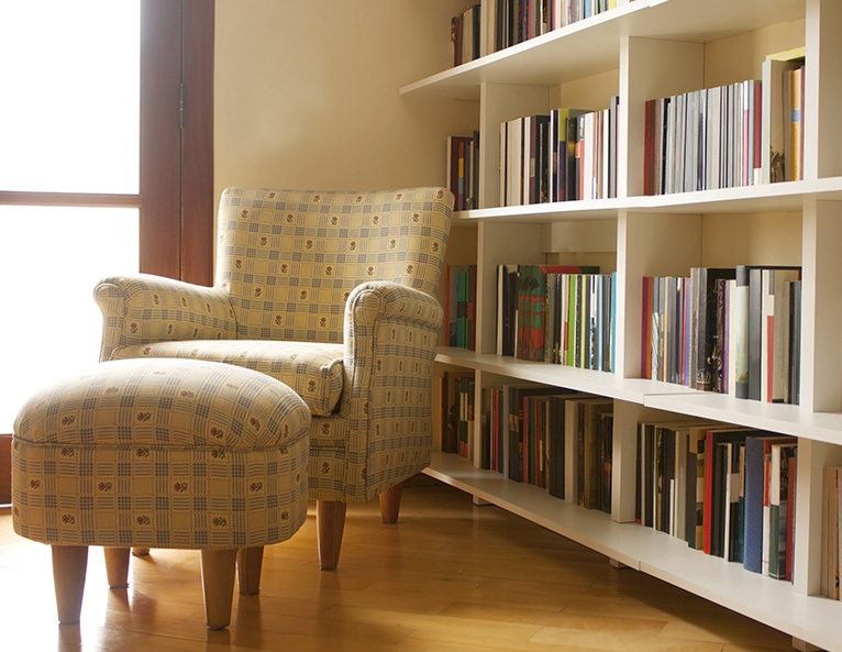 Reading chair and foot stool in room with many bookshelves