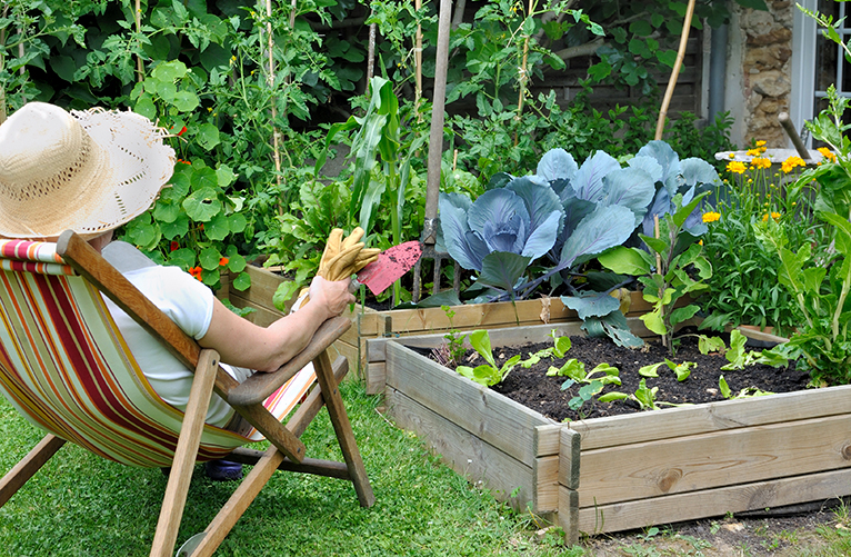 Lady relaxing by vegetable patch