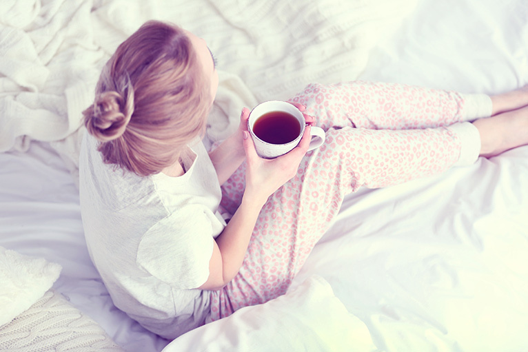 Girl sitting on a bed with a cup of tea