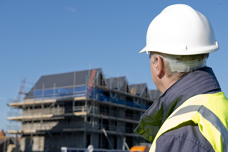Man in hard hat looking at unfinished apartment block