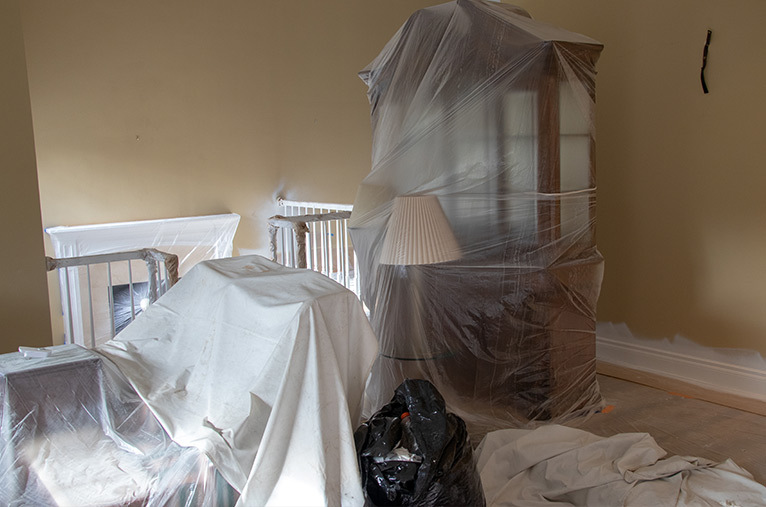 Room with furniture covered with dust sheets to prepare for home improvement work