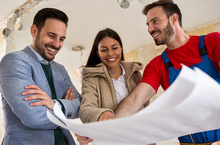 Three people discussing a blueprint to prepare for home improvement work