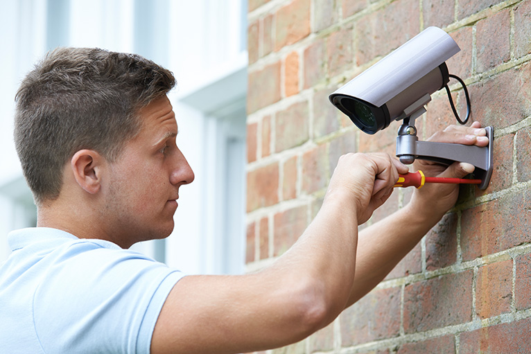 CCTV being fitted on an exterior wall