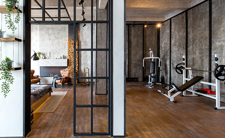 House extension with concrete walls and spotlights, split into a home gym and a bedroom