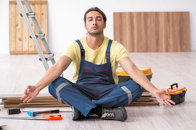 Tradesperson sitting down to meditate with tools and equipment in the background