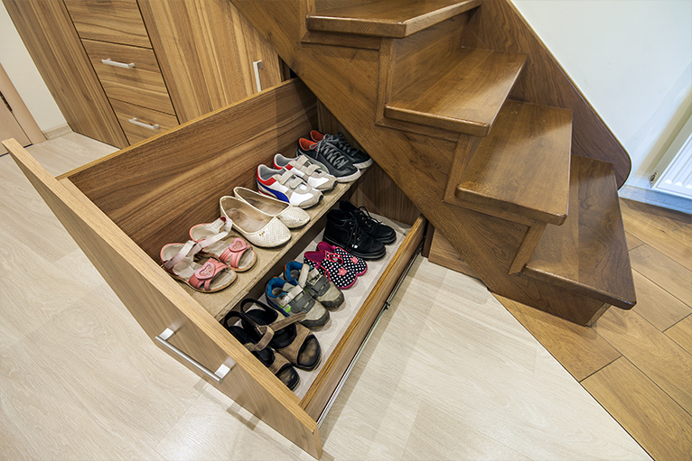 Wooden staircase with built-in drawer containing shoes pulled out