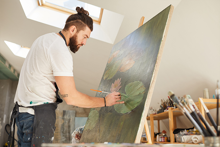 Man painting a dark green pond with lily pads on a canvas