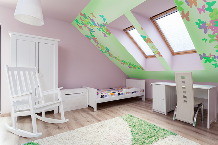 Pink kids' loft bedroom with a green feature wall that has multicoloured butterflies on it