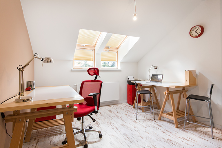 White office space with two desks and pops of the colour red from the desk chair, filing cabinets and hole punch