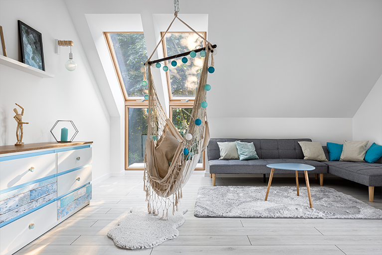 Bright living space loft conversion with a hanging chair and sofa