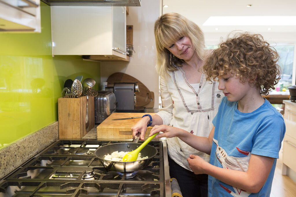 Mother helping her young son to cook on a gas hob
