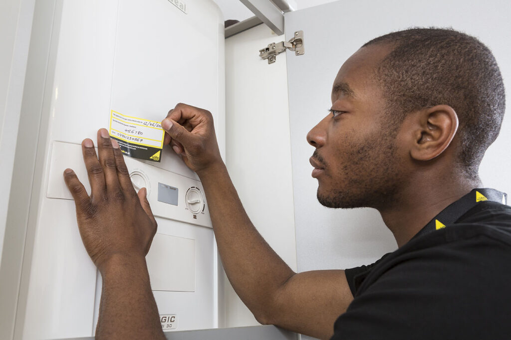 Gas Safe engineer attaching an annual service confirmation sticker to a boiler