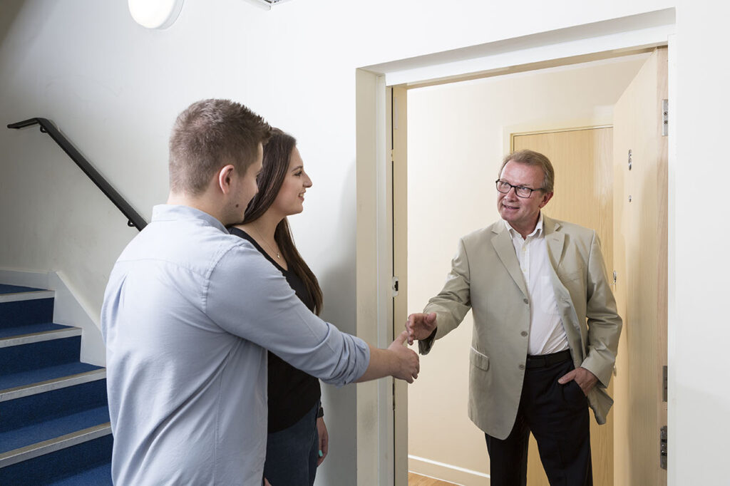 Landlord welcoming tenants into their new property
