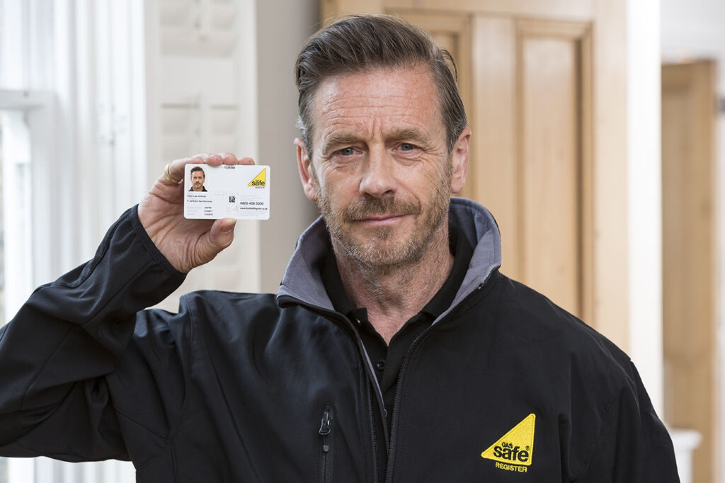 Gas and heating engineer holding his Gas Safe ID card