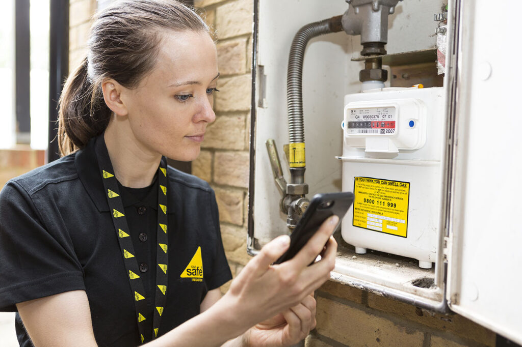 Female engineer checking a gas meter outside a home