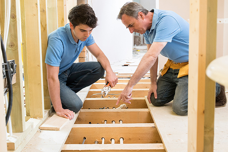 Floor fitter teaching apprentice on the job