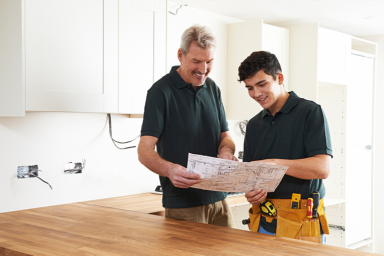 Electrician and apprentice smiling at site plans