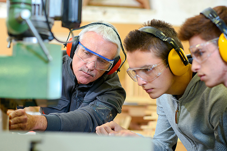 Tradesman teaching two apprentices