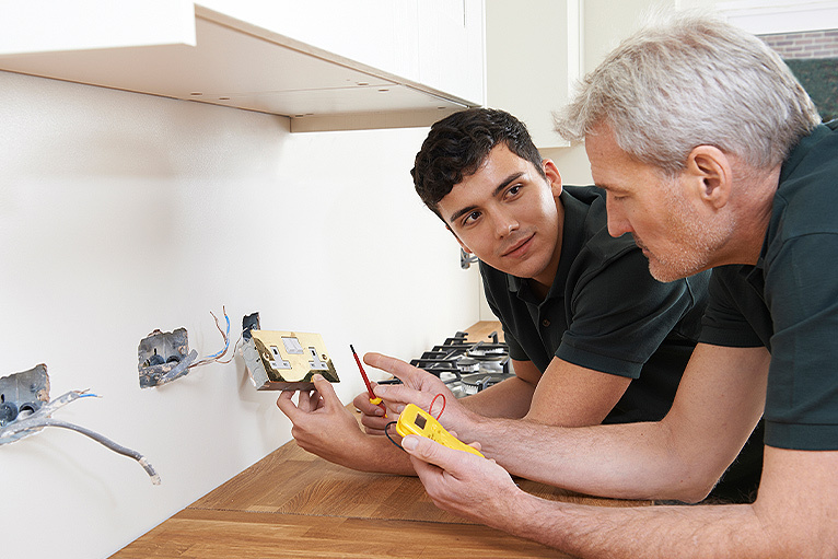Electrician teaching apprentice in a kitchen