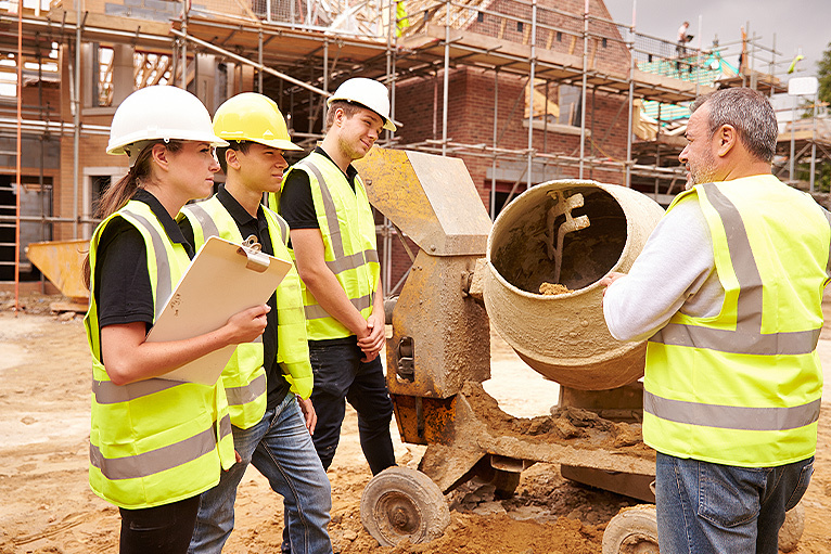 Builder and apprentices working on a housebuilding project