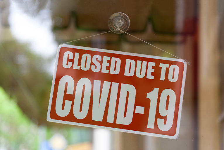 """Red closed sign on business door, reading """"Closed due to COVID-19"""""""