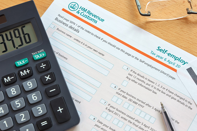 Self-assessment tax form, calculator and glasses on a table - coronavirus support