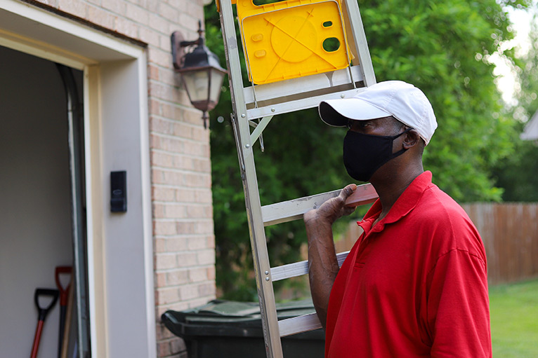 Tradesperson wearing a mask and carrying a ladder into a customer's home