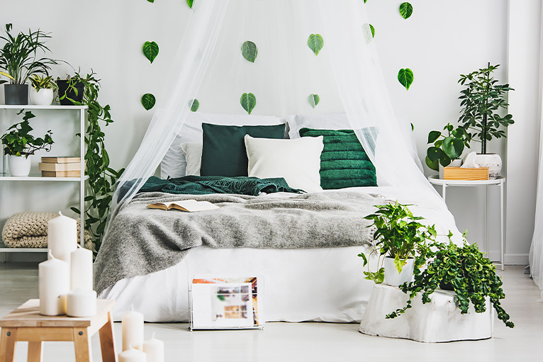 Bright and airy bedroom with plants and candles
