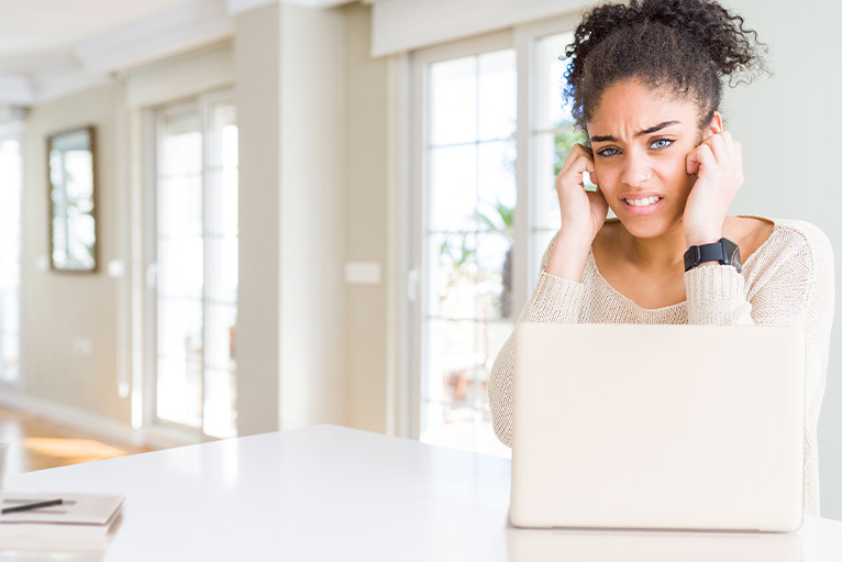 Woman with laptop, cringing from outside noise