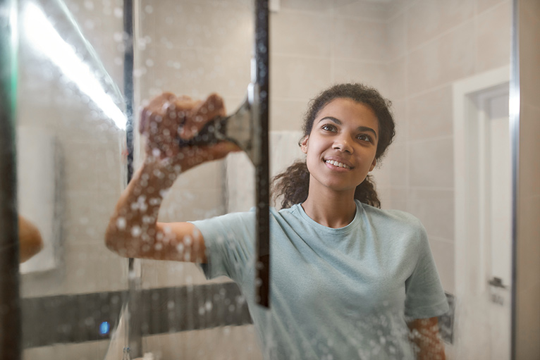 Smiling woman using a squeegee to clean her shower