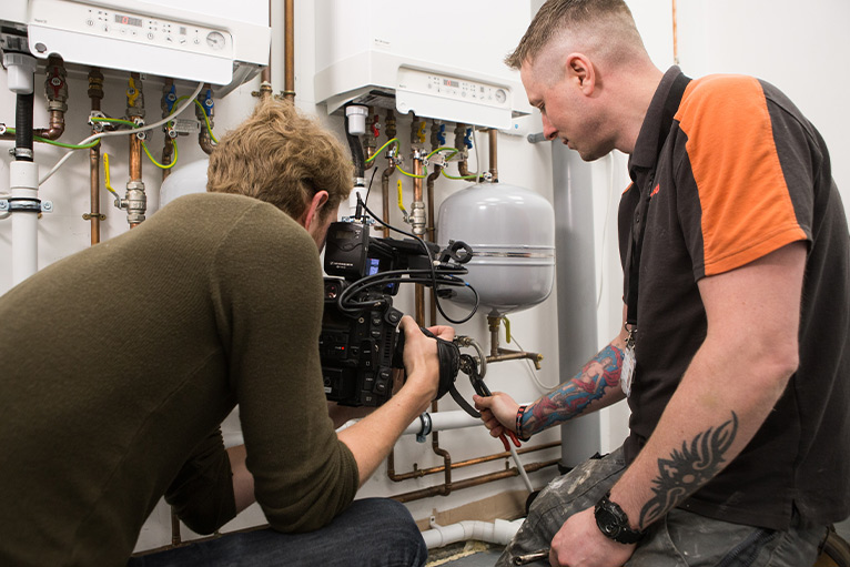 Social media: Person video recording a plumber working
