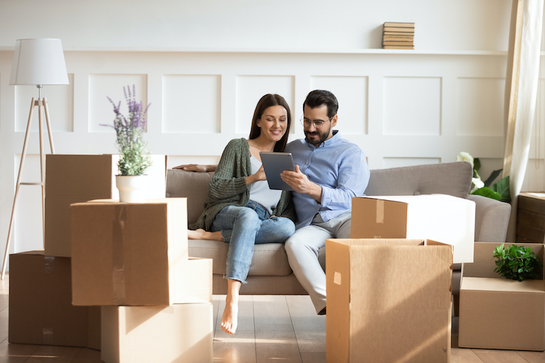 Couple looking at a tablet, surrounded by moving boxes