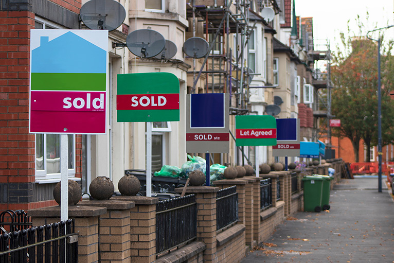 Estate agent signs outside a row of houses
