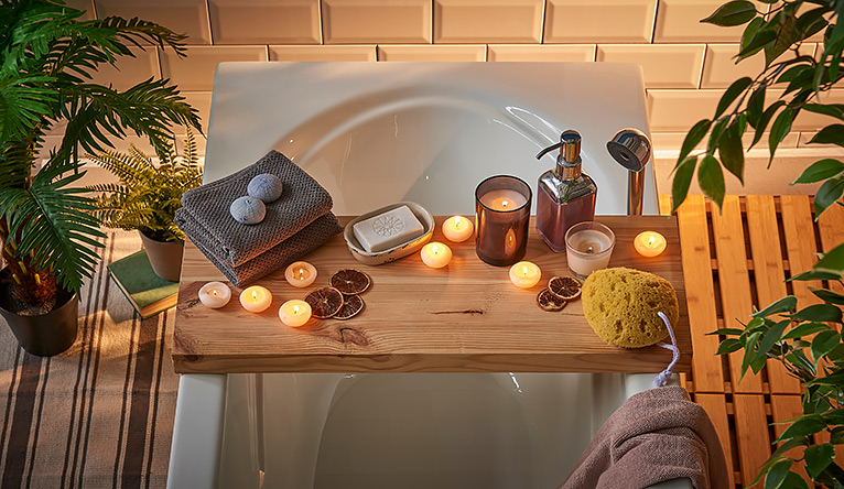 over-bath caddy holding candles, flannels and soap
