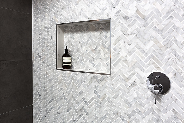 Grey herringbone tiles inside a shower