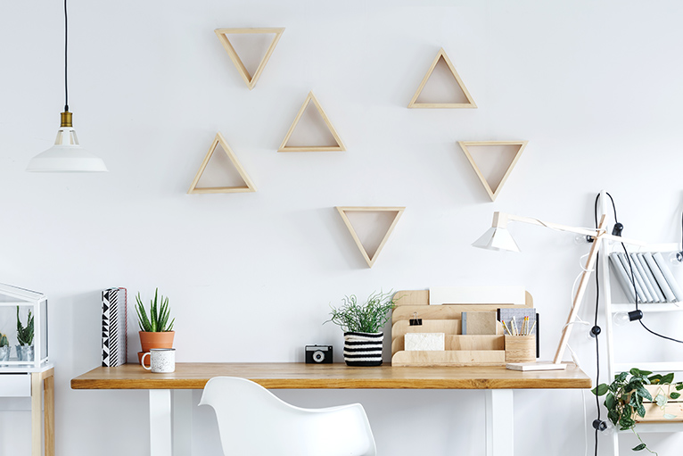 Desk in front of a wall with a wooden geometric cut out design