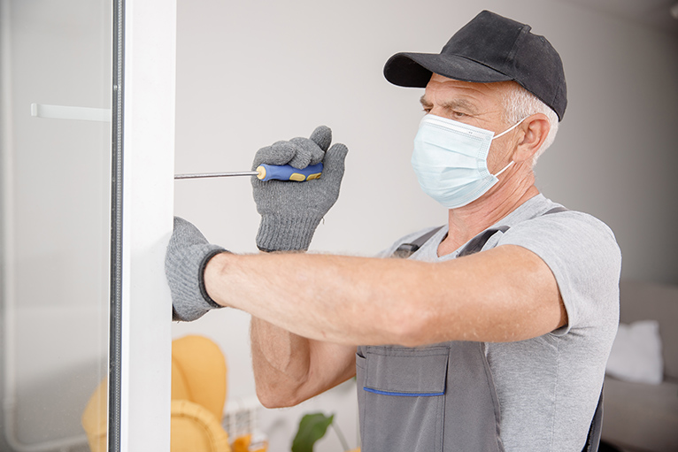 Window fitter working inside a home, wearing a face mask