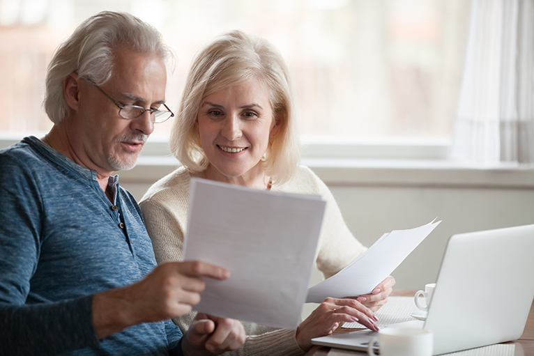 Smiling older couple looking at laptop and paperwork