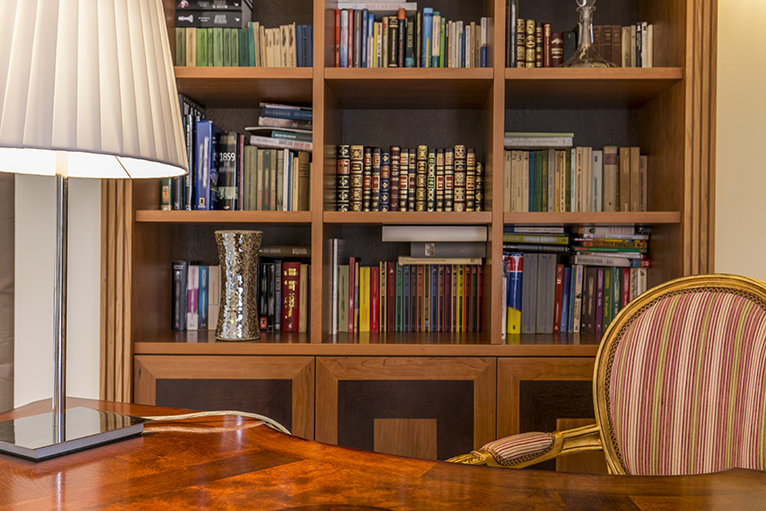 Wooden bookcase with colourful books in home office